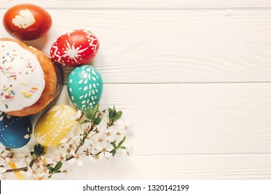 Colorful easter eggs near Easter bread, kulich near eggs and apple blossom white flowers on wooden background, flat lay view of easter dinner