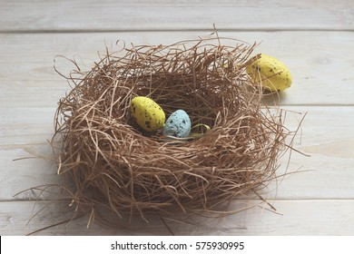 Colorful Easter eggs in the nest of a bird on a wooden board.