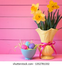 Colorful Easter Eggs in Nest with Daffodils in Vase on Pink Boards Background with room or space for copy, text, or your words.  Vertical