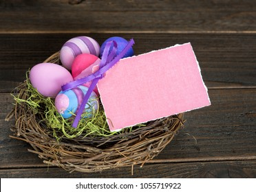 Colorful Easter Eggs in Nest on Rustic, Dark barn wood board backgroound with empty Pink Card with room or space for your words, copy, or text.  Horizontal is a flat lay from above, looking down view