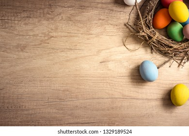 Colorful Easter eggs in nest with tulip flower on rustic wooden plank background. Holiday in spring season. Vintage pastel color tone. Top view composition