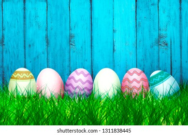 Colorful easter eggs on the grass with blue wooden fence background. Happy Easter