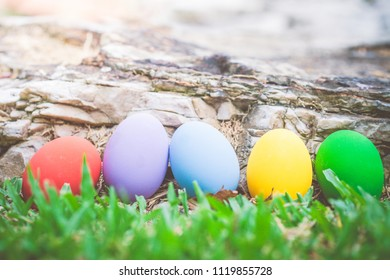 Colorful easter eggs on natural stone texture and green grass background