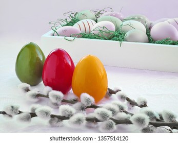 Colorful Easter eggs on the table and a white tray with more Easter eggs