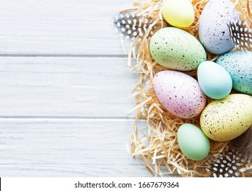 Colorful Easter eggs on white wooden background.  Easter holiday concept, flat lay, top view.
