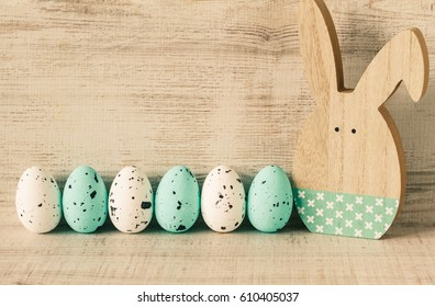 Colorful easter eggs on wood background with rabbit toy.