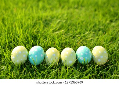 Colorful Easter eggs painted in pastel colors on grass background.