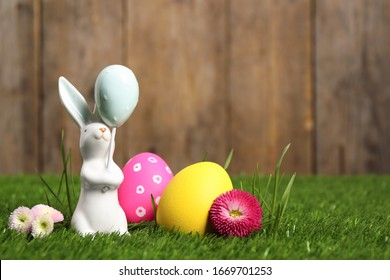 Colorful Easter eggs, rabbit and daisy flowers on green grass. Space for text