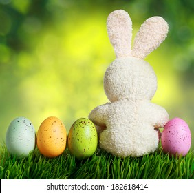 Colorful easter eggs and rabbit on green grass over bokeh