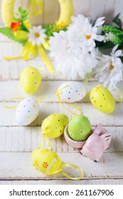 Colorful easter eggs and rabbit  on white  wooden background. Easter background. Selective focus is on rabbit.