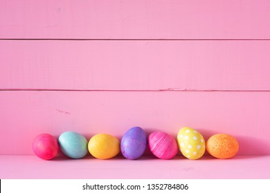 Colorful Easter Eggs in a Row on a Table and against a Bright Pink Board Wall Background with copy space. Horizontal and wide with side view