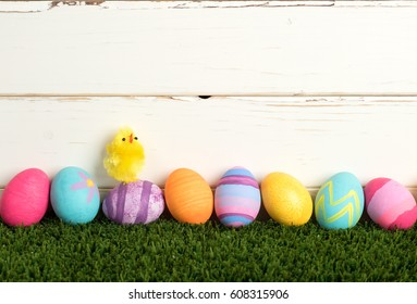 Colorful Easter Eggs in a Row on Grass against a Distressed White Wood  Board Wall Background with room or space for copy, text, or your words.  It's a horizontal with a Cute Baby Chick Singing.