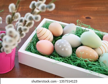 Colorful Easter eggs in a white tray with green grass and pussy willow branches over wooden table