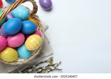 Colorful Easter eggs in wicker basket and willow branches on white wooden table, flat lay. Space for text