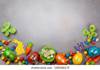 Colorful Easter eggs,chocolate Easter sweets, bunny and nest with chicks  on grey background. Top view with copy space. Festive Easter concept.