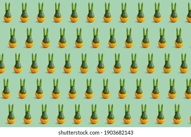 Colorful easter pattern of green avocado bunny in green and orange. Minimal background. Front view.