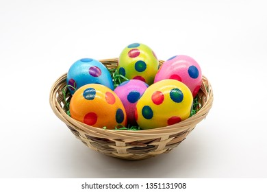 colorful eggs in a basket, isolated on white background