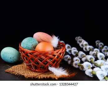 Colorful eggs in basket with pussy willow over dark background, Easter concept.