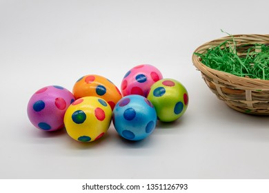 colorful eggs in front of a basket