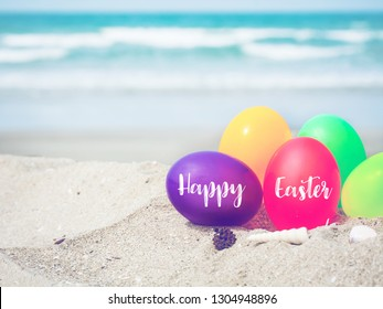 colorful eggs on white sand beach over blue sea,happy Easter or summer holiday concept.