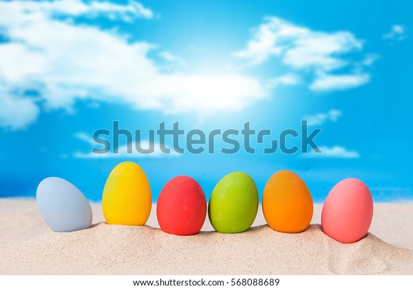colorful eggs on white sand beach over cloudy sky,happy Easter or summer holiday concept.