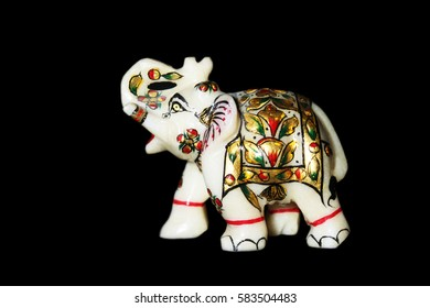 Colorful elephant figurine from mineral rock isolated on black blackground.