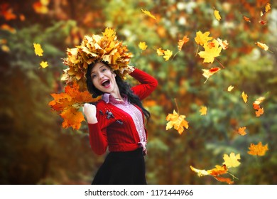 Colorful emotional portrait of a beautiful girl in autumn. Maple yellow and red leaves scatter everywhere.