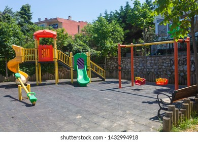 Colorful and empty playground in the park among the houses. Children run, slide, swing,seesaw on modern playground. Urban neighborhood childhood concept.