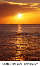 Colorful empty seascape with shiny sea over cloudy sky and sun during sunset in Cozumel, Mexico