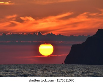 Colorful, enchanting in its beauty sunset in the Crimea, Ukraine. Delicate, fluffy, lemon-colored sun, slowly descending and disappearing into the sea. And only a riot of color and flashes of orange