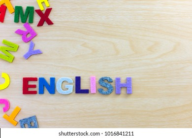 Colorful english alphabet sponge on wooden table background. ABC,Cube foam english letters on wood desk background.    Learn english concept. top view.