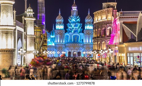 Colorful Entrance to Global Village with crowd  in Dubai, UAE. Brightly colouredl lights and highly detailed pavilion facades have helped make Global Village one of Dubai's most popular attractions