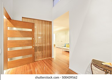 Colorful entrance and wooden door with designs, walls are painted with white color, floor is polished and very shiny look, lightning is perfect, sofa set and white cupboard can see in the room.