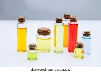 Colorful essence oil bottles on white background