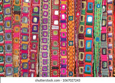 Colorful ethnic belts with mirrors at market in GOA, India. Tibetan souvenirs.
