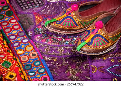 Colorful ethnic shoes, cushion cover and Rajasthan belts on flea market in India