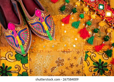 Colorful ethnic shoes and gipsy belt on yellow Rajasthan cushion cover on flea market in India