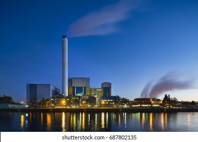 Colorful evening view of a modern waste incineration plant in Oberhausen, Germany with blue sky.