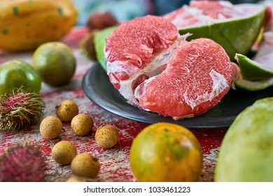 Colorful exotic fruit on the shabby wooden red table. There is a sliced pomelo on the black plate, citrus, lychees, papaya and rambutans. Closeup horizontal photo.