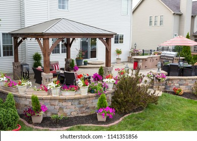 Colorful exterior curved patio with summer flowers and comfortable wicker armchairs under a covered wooden gazebo with aluminum roof in a neat upscale backyard