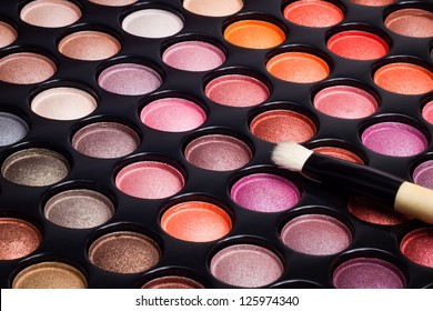 Colorful eye shadows palette with professional makeup brush. Makeup background