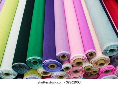 Colorful fabric rolls. Focus on front part of rolls.