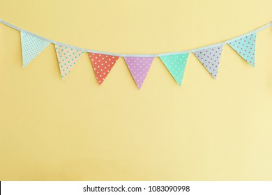Colorful fabric vintage party flag hanging on yellow wall background
