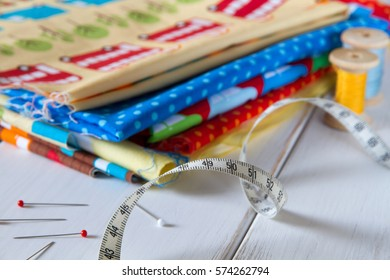 Colorful fabrics in blue, yellow, red, orange and green with pins, measuring tape and cotton threads on white wooden table