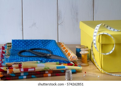 Colorful fabrics in blue, yellow, red, orange and green with pins, yellow box, black vintage scissors and cotton threads on white wooden table