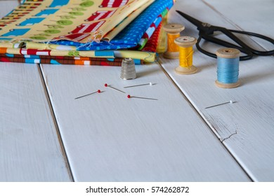Colorful fabrics in blue, yellow, red, orange and green with pins and cotton threads on white wooden table