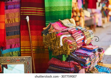 Colorful fabrics and carpets for sale on a street in Medina of Chefchaouen, Morocco, small town in northwest Morocco known for its blue buildings