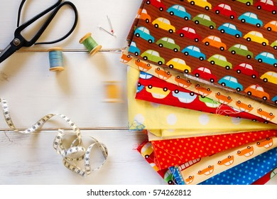 Colorful fabrics with vintage scissors, measuring tape and cotton threads on white wooden table