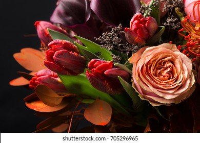 Colorful fall bouquet on black background. Autumn composition of roses, tulips, dry leaves and herbs closeup. Flower shop and florist design concep