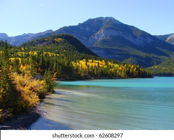 Colorful fall foliage surrounding a clear blue lake in the mountains